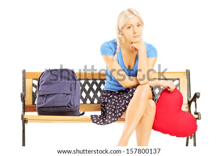 Sad female student sitting on a wooden bench and holding a red heart isolated on white background - stock photo
