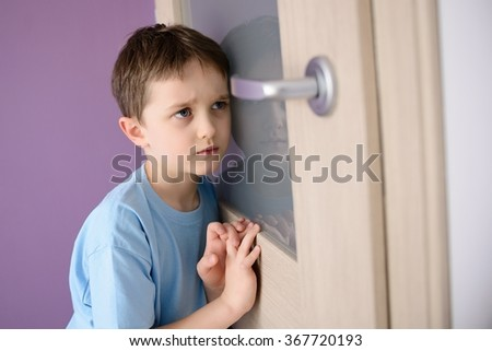 Sad, frightened child listening to a parent talking through the door with a glass pressed to his ear. - stock photo
