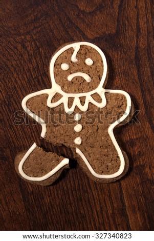 Sad gingerbread man - cookie with a broken leg. - stock photo