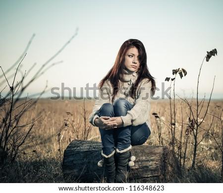 sad girl at fall season meadow - stock photo