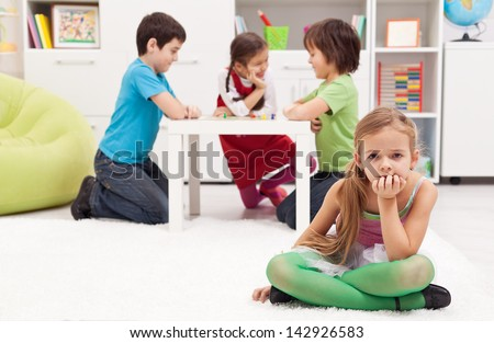 Sad girl feeling excluded from the group of playing kids - stock photo