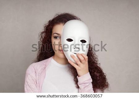 sad girl hiding behind mask - stock photo