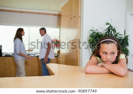 Sad girl listening to her fighting parents - stock photo