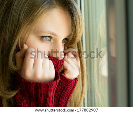 sad girl looking out the window waiting for her husband, in the house - stock photo