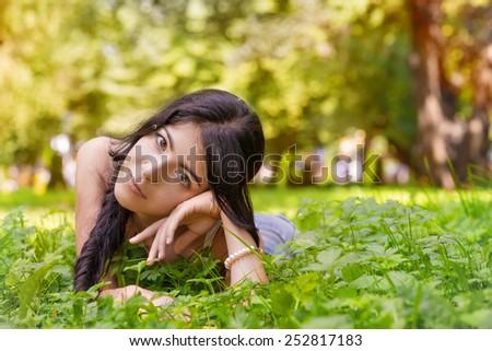 sad girl lying in summer grass - stock photo