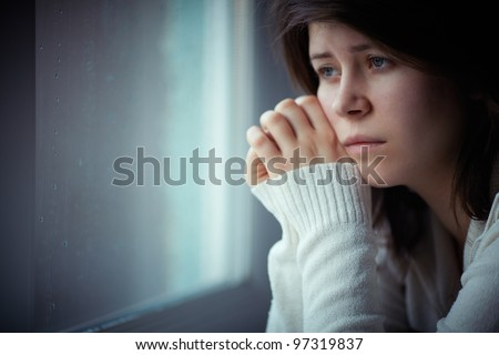 sad girl near window thinking about something - stock photo