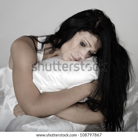 sad girl on a bed - stock photo