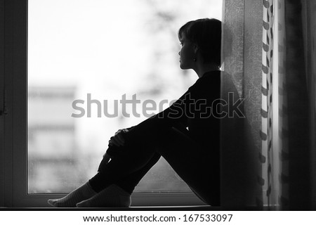 sad girl on the windowsill looking out the window - stock photo