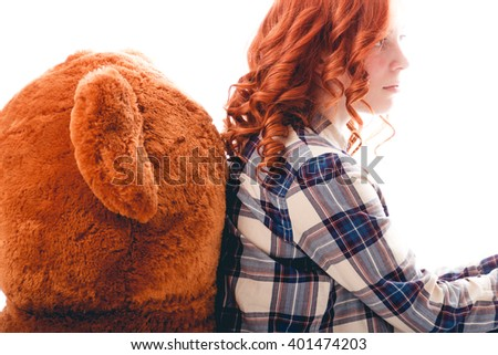 Sad girl sitting against the bear in despair - stock photo