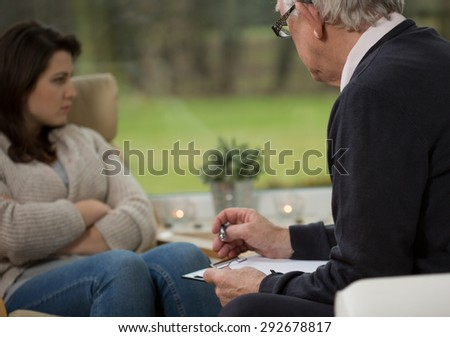 Sad girl sitting on chair during psychotherapy session - stock photo