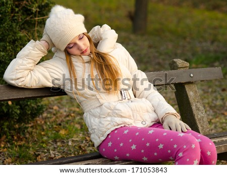 Sad girl sitting on the bench in the park on beautiful autumn day. - stock photo