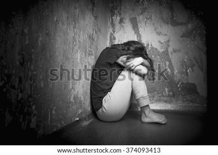 Sad girl sitting on the floor in corner of room - stock photo