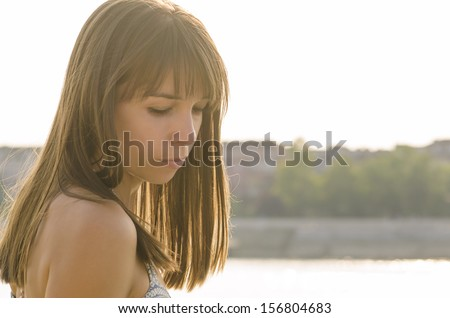 Sad girl standing by the river, pondering. - stock photo