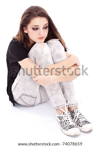 Sad girl teenager sits twining arms about legs. Isolated on a white background. - stock photo