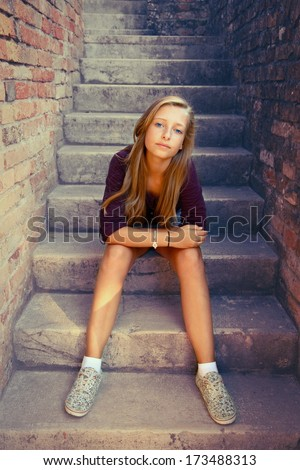 Sad girl with blue eyes sitting at stone brick stairs, soft focus - stock photo