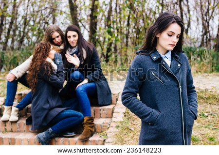 Sad girl with friends gossiping in background,  behind her back - stock photo