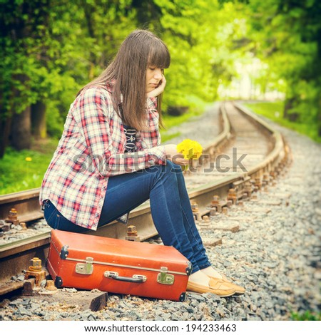 sad girl with retro suitcase and bouquet of dandelions sitting on the rails - stock photo