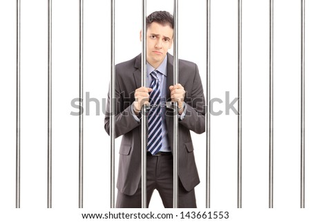 Sad handcuffed businessman in suit posing in jail and holding bars, isolated on white background - stock photo