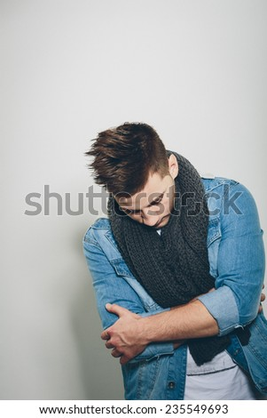 Sad Handsome Man Wearing Denim Jacket and Gray Knitted Scarf, Crossing his Arms in Front his Body While Looking Down. Isolated on Light Gray Background. - stock photo