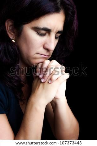 Sad hispanic woman praying with a sad face isolated on black - stock photo