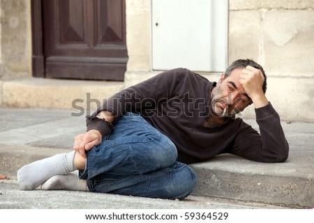 sad homeless man lying on sidewalk and smoking cigarette - stock photo