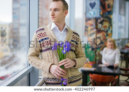 sad in love guy with holding flowers waiting for someone. man waiting for the boyfriend or girlfriend on a date. behind the man lonely girl sitting at a table in a cafe. - stock photo