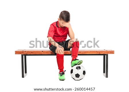 Sad kid in soccer uniform sitting on a bench isolated on white background - stock photo