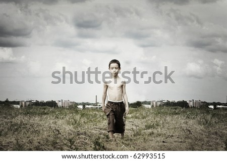 sad kid is walking in the field against ugly industrial background with artistic shadows added - stock photo