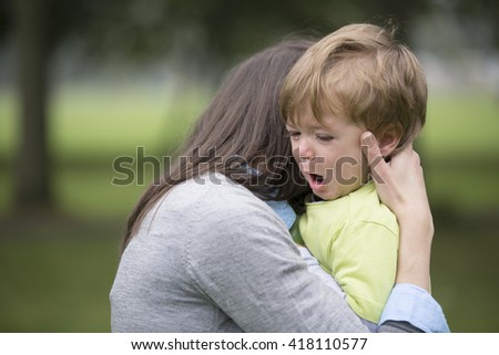 Sad little boy being hugged by his mother. Parenthood, Love and togetherness concept. - stock photo