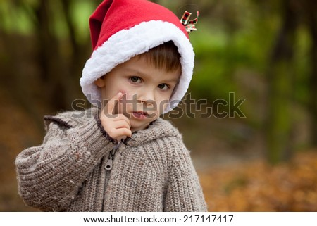 Sad little boy in the park, with santa hat, showing his hurt cheek from a falling, looking at the camera - stock photo