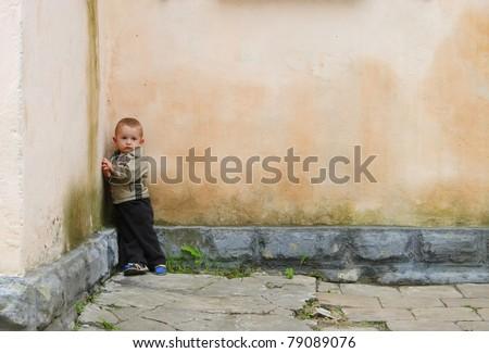 sad little boy in the yard - stock photo