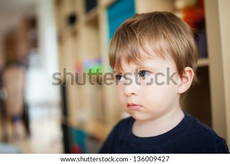 Sad little boy inside a house - stock photo