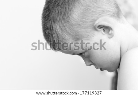 sad little boy looking down towards the floor - stock photo