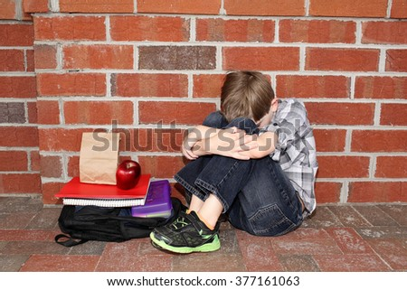 Sad little boy outside of school - stock photo