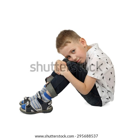 Sad little boy sits on floor embracing his knees isolated on white background with shadow - stock photo