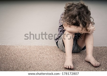 sad little boy sitting near the wall - stock photo