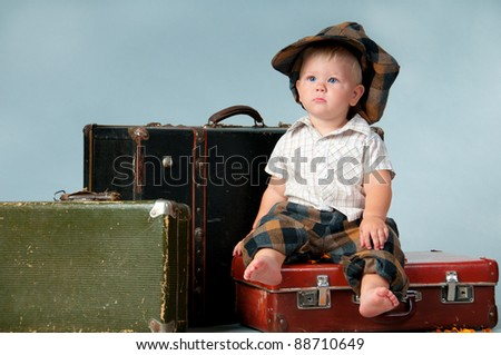 Sad little boy sitting on an old suitcase. He is wearing a hat - stock photo
