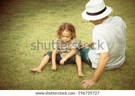 sad little boy sitting on the grass with dad - stock photo