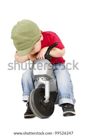 Sad little boy sitting on the motorcycle. Isolated on white. - stock photo