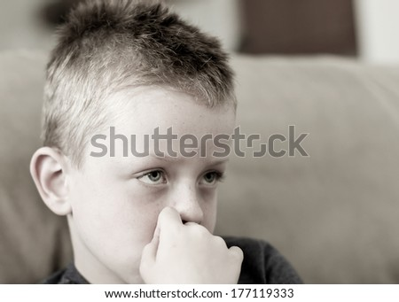 Sad little boy with a fearful expression - stock photo