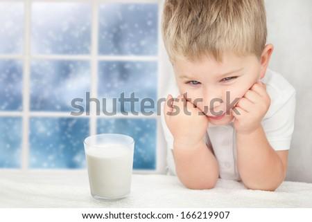 Sad little boy with glass of milk - stock photo