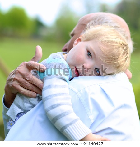 Sad little child, adorable blonde toddler girl, relaxing and comforting on the shoulder of her grandparents - stock photo