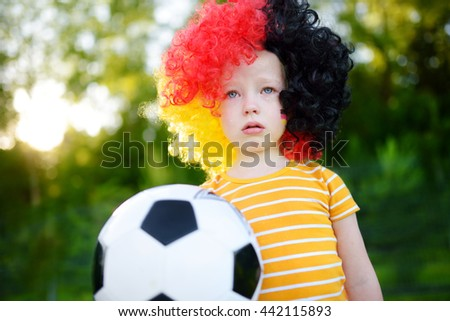 Sad little german child crying over her national football team's loss in soccer championship - stock photo