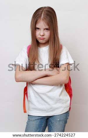 Sad little girl and school bag - stock photo