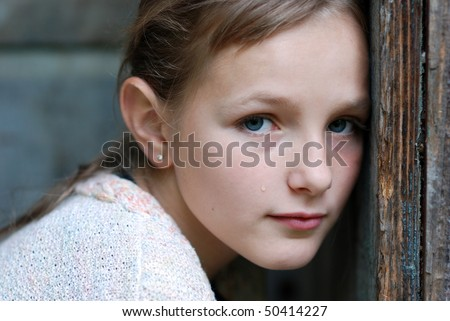 Sad little girl is looking with serious face at camera. - stock photo