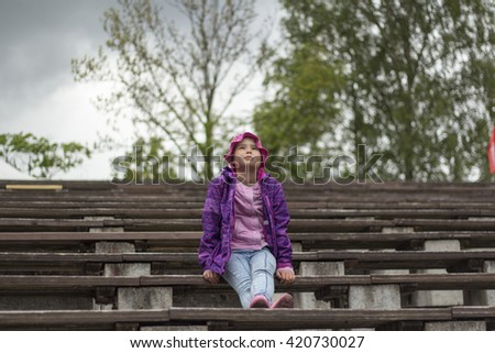 Sad little girl is sitting on the bench - stock photo