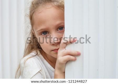 Sad little girl near the white wall. - stock photo