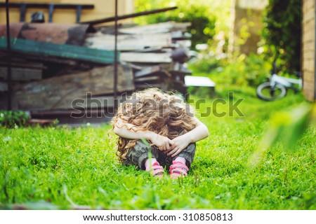Sad little girl on outdoors. - stock photo