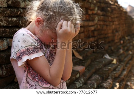 Sad little girl on the background of an old brick wall - stock photo