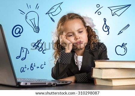 Sad Little Girl Sits At Table With Books Near Laptop On Blue Background. Back To School Theme - stock photo